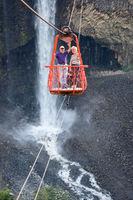 Senior tourists gliding on the zip line trip against Bridal veil (Manto de la novia), waterfall in Cascades route, Banos de Agua Santa