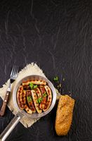 Fried sausages with parsley, bread and fork in a pan on black background