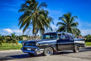 HDR - Schwarzer amerikanischer Oldtimer parkt unter blauem Himmel nahe des Strandes in Varadero Kuba