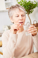 Alte kranke Frau nimmt eine Tablette
