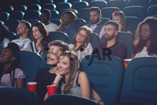 Young couple embracing in cinema and watching movie.