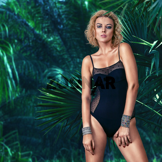 Fashion model in lingerie posing in tropical forest