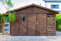 Garden shed exterior in Spring, with woodshed
