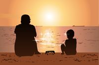 Father and son sitting on the beach and watching sunset