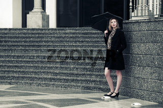Young fashion woman with umbrella at the wall
