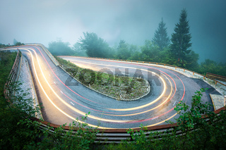 Winding mountain road with car lights. Foggy wet weather and low visibility. Alps, Slovenia.