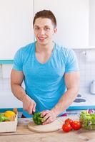 Essen zubereiten Gemüse schneiden junger Mann Mittagessen in der Küche Hochformat gesunde Ernährung