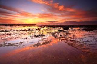 Sunrise skies reflecting on the exposed rocks in low tide