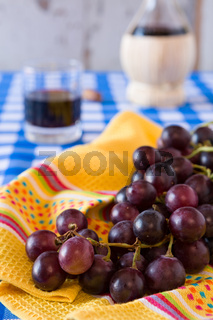 Closeup of a bunch of red grapes and a glass of red wine with a wine flask