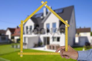 Makler mit Meterstab und Immobilie