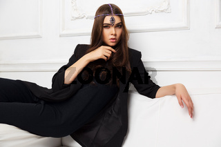 Young fashion woman in black jacket sitting on sofa at home