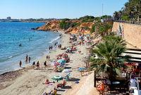 People sunbathing on the rocky beach of Punta Prima. Spain