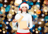 smiling woman in santa hat opening christmas gift