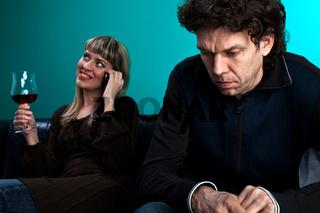 Frau am Telefon und ein frustrierter Mann