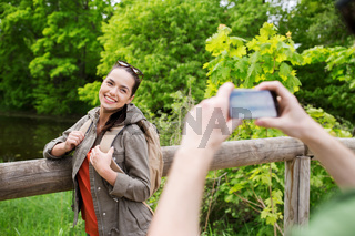 couple with backpacks taking picture by smartphone