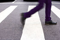 Man crossing the street. Social shoes and purple pants.