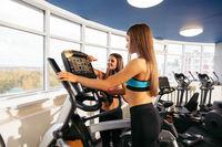 Slim girls on exercise bikes installing programme