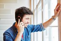 Junger Mann mit Smartphone verabredet sich