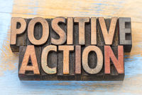 positive action - word abstract in wood type