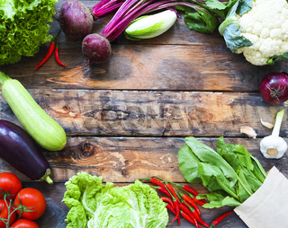 Raw organic natural vegetables on wooden background
