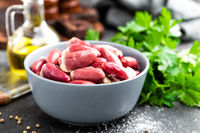 Fresh raw chicken hearts on dark background