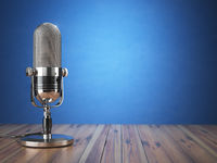 Retro old microphone. Radio show or audio podcast concept. Vintage microphone on blue background.