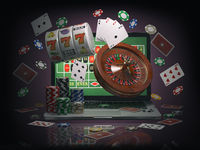 Online casino concept. Laptop with roulette, slot machine, casino chips and playing cards isolated on black background.