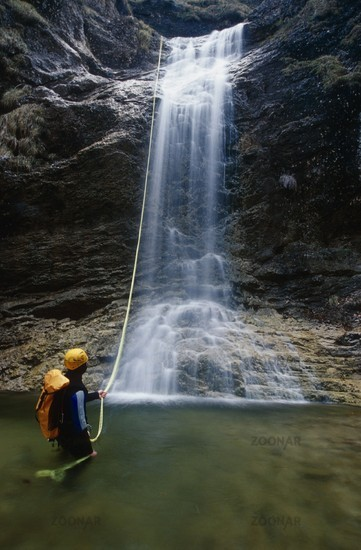 Ein Mann beim Abziehen des Seiles vor einem Wasserfall beim Canyoning