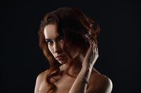 Studio portrait of beautiful sad girl posing nude