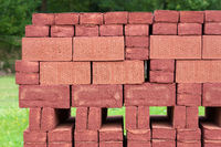 Stack of piled red bricks outside