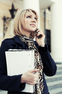 Happy young business woman calling on cell phone