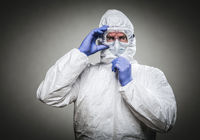 Man With Intense Expression Wearing HAZMAT Protective Clothing Against A Gray Background.