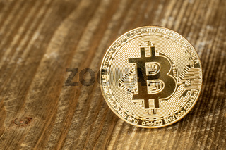 One bitcoin on wooden background