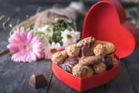 Delicious sweets in a red box and flowers