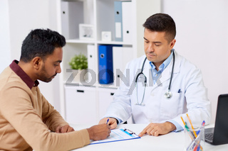 doctor and patient signing document at clinic