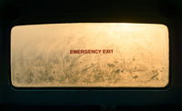 Emergency exit sign on a misty window