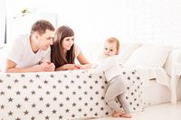Parents teach the child to climb on the bed