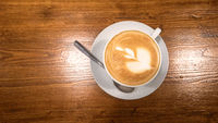 Top view of cappuccino coffee with art dress up in white cup on polished wooden table