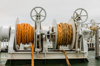 Two winches with orange rope on a ferry, white cloudy backgrond