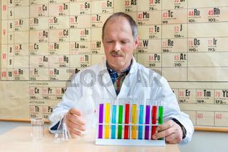 Chemistry teacher filling colorful test tubes