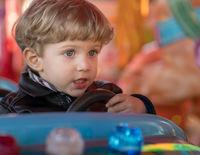 Baby boy drives blue car at carousel