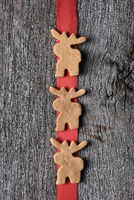 Three moose shaped cookies on a red ribbon. Vertical and hanging on a rustic wood wall.
