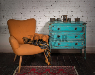 Vintage orange armchair, blue cabinet and ornate scarf
