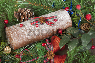 Frosted christmas chocolate log with glittered bells and pine cones