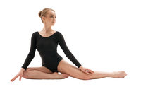 Young gymnast in black sits on the floor in studio