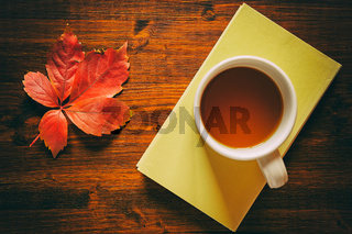 Cup of tea on a book and autumnal leaf