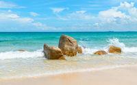 Clear azure sea crashing on rocks