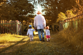 kids walk with grandfather in summer