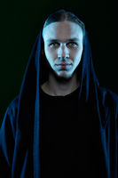 Young blond mystic man in hood on black