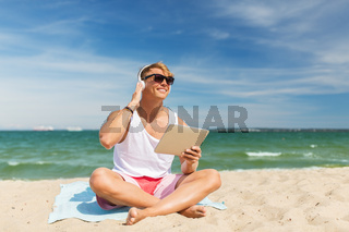 happy man with tablet pc and headphones on beach